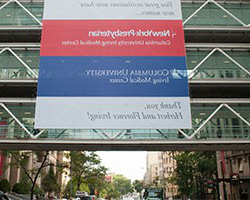 Red, blue and white banner hanging over a glass building