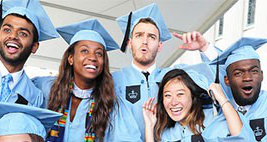 Five graduates in cap and gown celebrate facing the camera