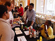 Two local small business owners sitting behind a table urge two attendees to a business fair to sample their organic juice product.