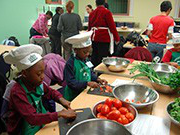 Wearing aprons and chef hats, a group of young children slice and dice an array of fresh vegetables.