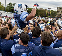The Columbia Lions football team lifts a teammate into the air in celebration.