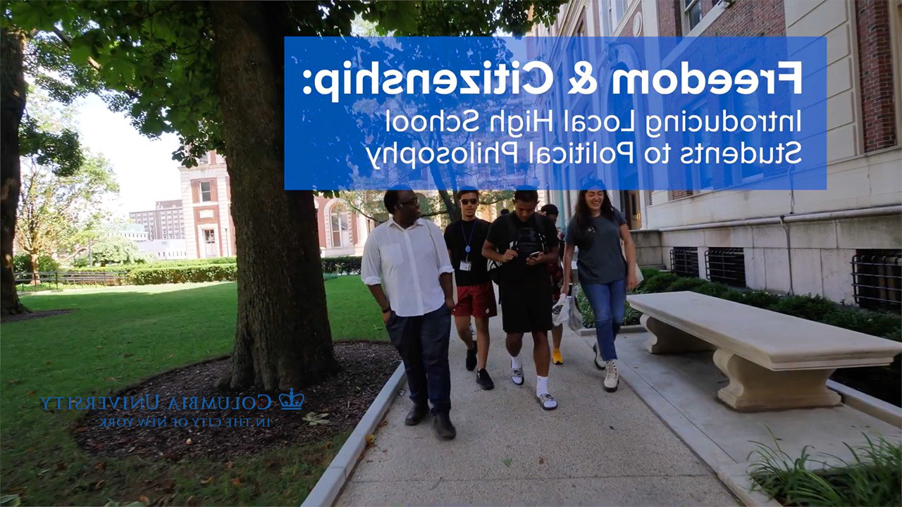 A group of high school students with down a sidewalk with a mentor between a green lawn and a building.